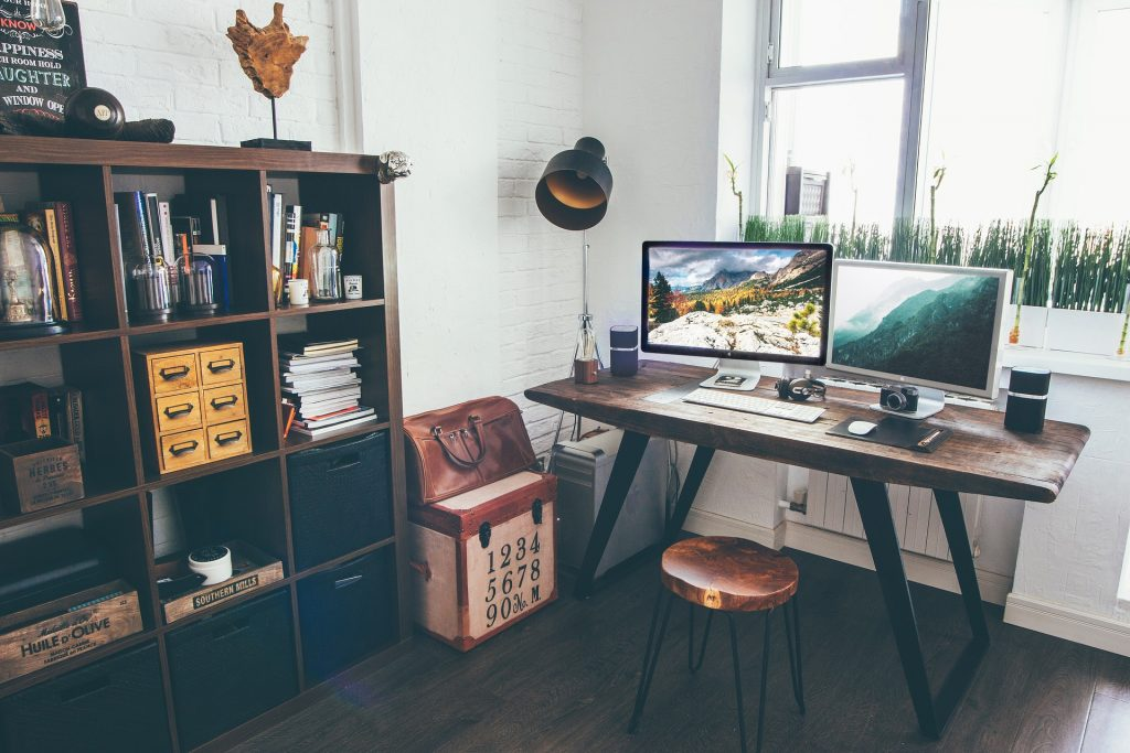 Desk with a two monitor computer on it and shelving with cubbies for craft room storage ideas.
