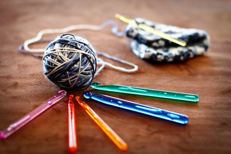 Five different colored crochet hooks surrounding a blue and yellow ball of yarn with a hat started in the background on brown carpet.