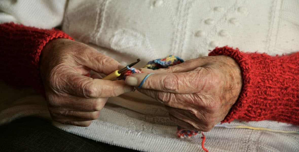 an older woman in white with red sleeves doing crochet with multicolored yarn with mainly her hands in the frame.