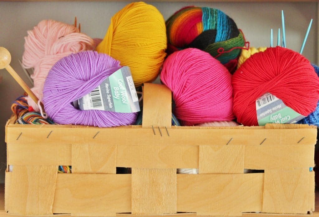 craft room storage ideas: Wooden basket with yellow, light pink, hot pink, light purple and multi colored balls of yarn.