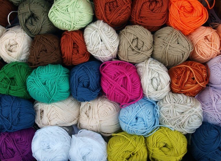 multiple bundles of different colored yarn for crochet stacked on top of each other.