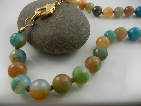 Round earth toned beaded necklace, with a gold clasp, draped across a stone -- bead crafts