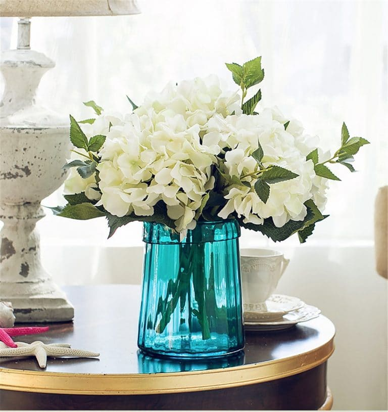 White flowers in a blue vase, great option when choosing the best florals for your home