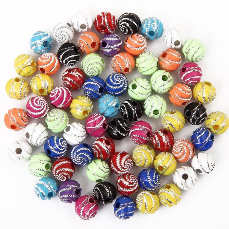 An assortment of acrylic beads in a variety of colors with swirly designs on them in sparkly silver.