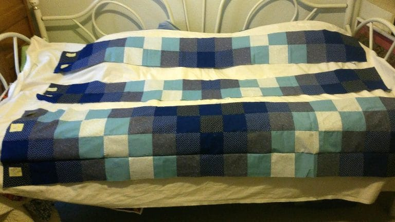 An unfinished blue and white quilt with yellow Post-it notes pinned along one side.