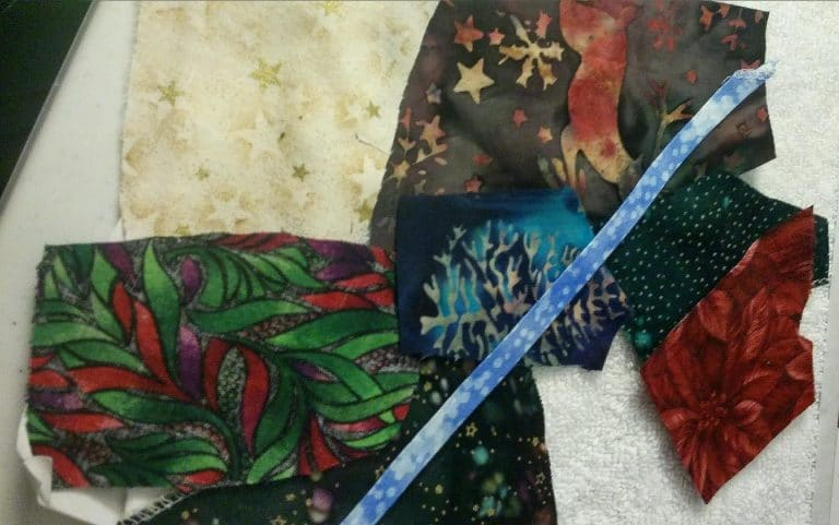Scraps of quilting material with woodland and winter colors and themes.