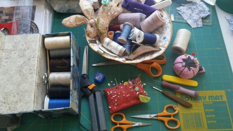 Quilting tools, including thread, scissors, pins, pincushions, and a cutting mat.