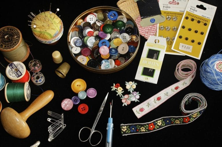 A collection of sewing tools you need to learn how to sew on a button. They include such as scissors, thread, needles, pins, and buttons.