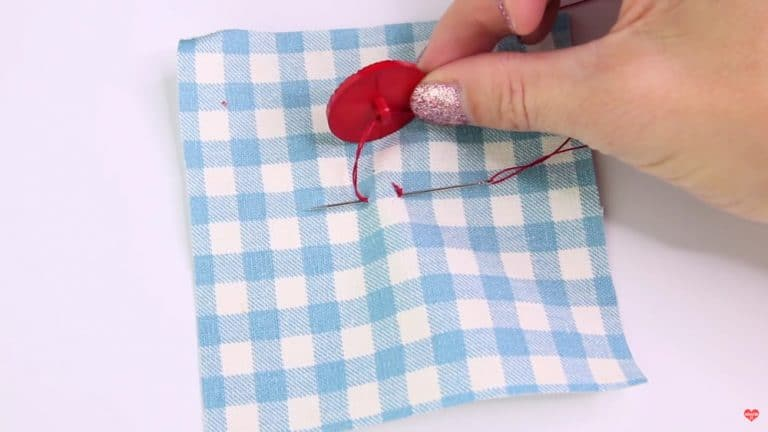 A person sewing a button with a single shank on the back onto a piece of fabric. Knowing how to sew on a button is an important skill.