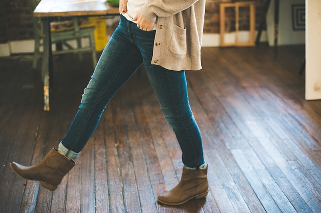 A woman wearing denim skinny jeans, boots and a cotton sweater.