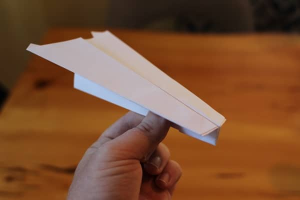 hand holding the best paper airplane